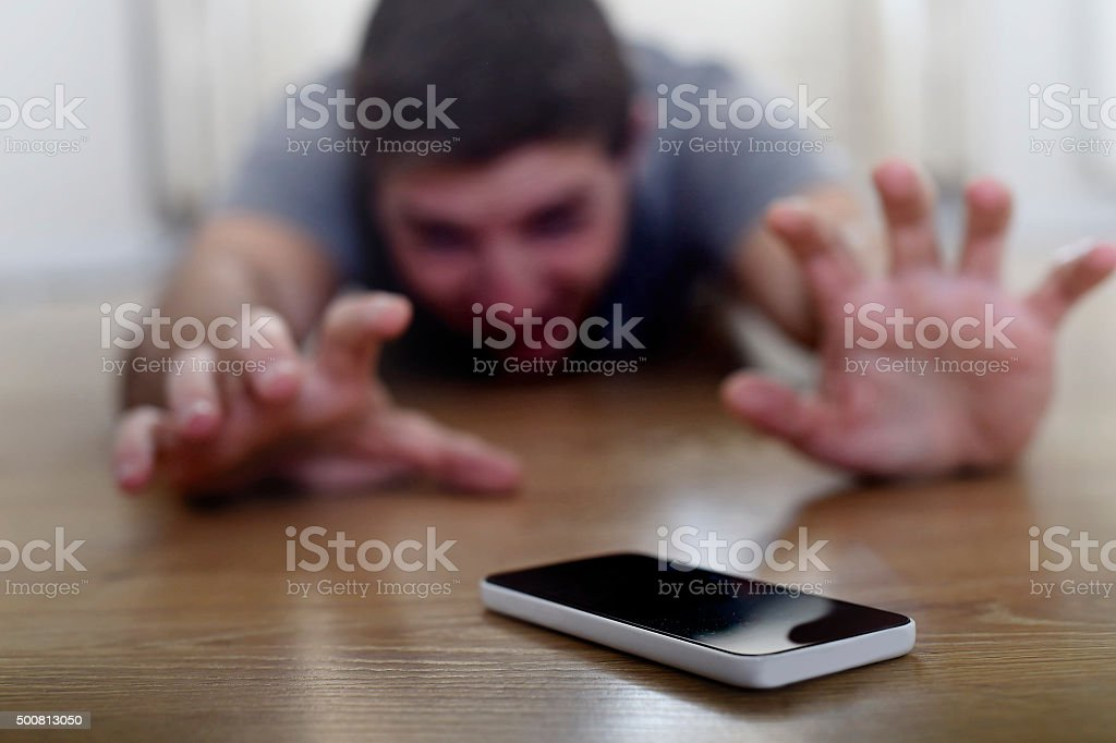 man creeping on ground smart phone and internet addiction concept stock photo