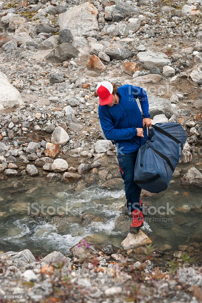 Man crosses stream carrying duffelbag stock photo