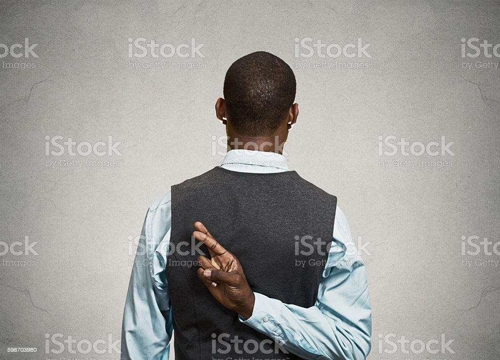 Man crossing fingers behind his back stock photo