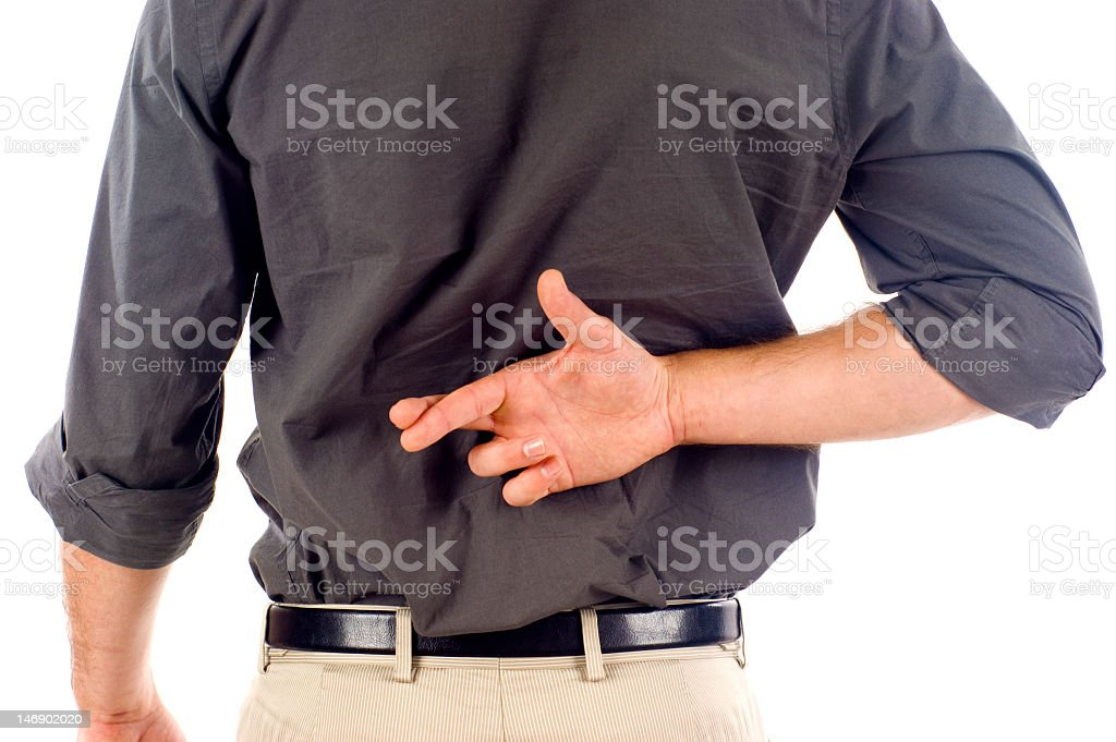 A man crossing his fingers behind his back indicating a lie royalty-free stock photo