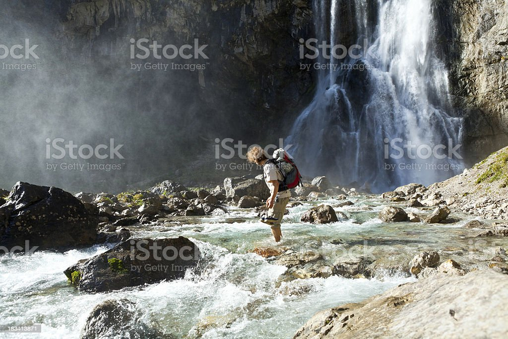Man crossing mountain river royalty-free stock photo