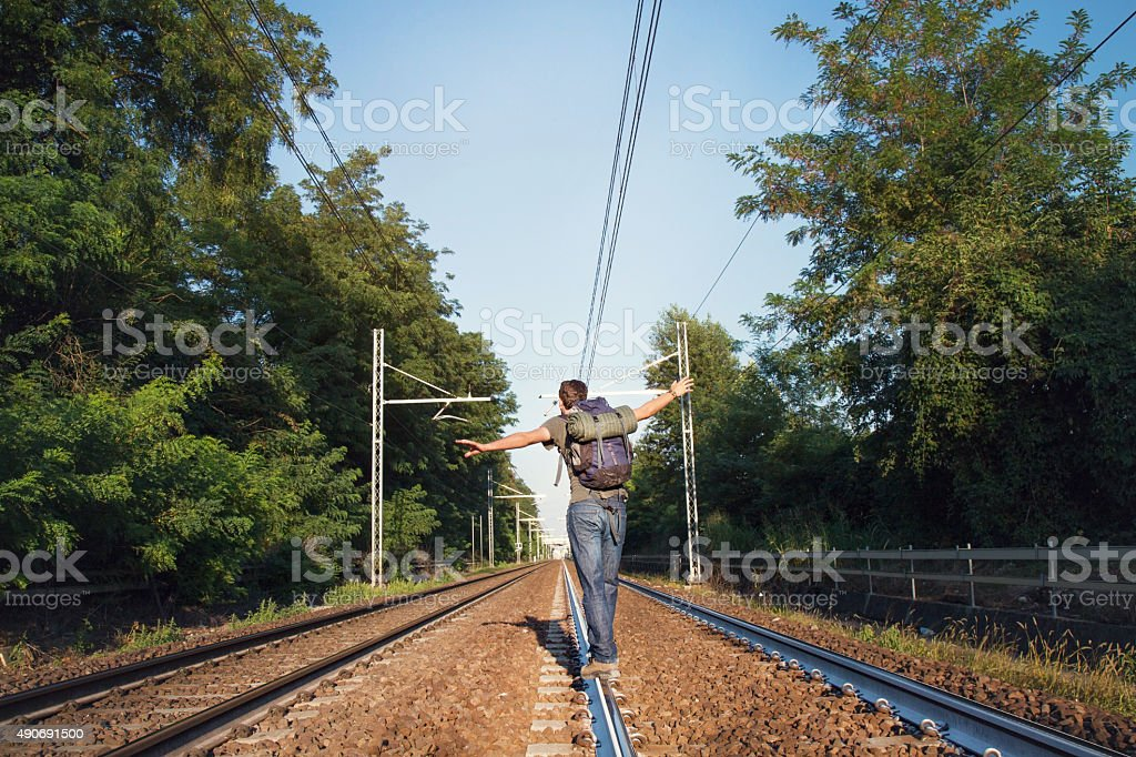Man crossing rail way stock photo