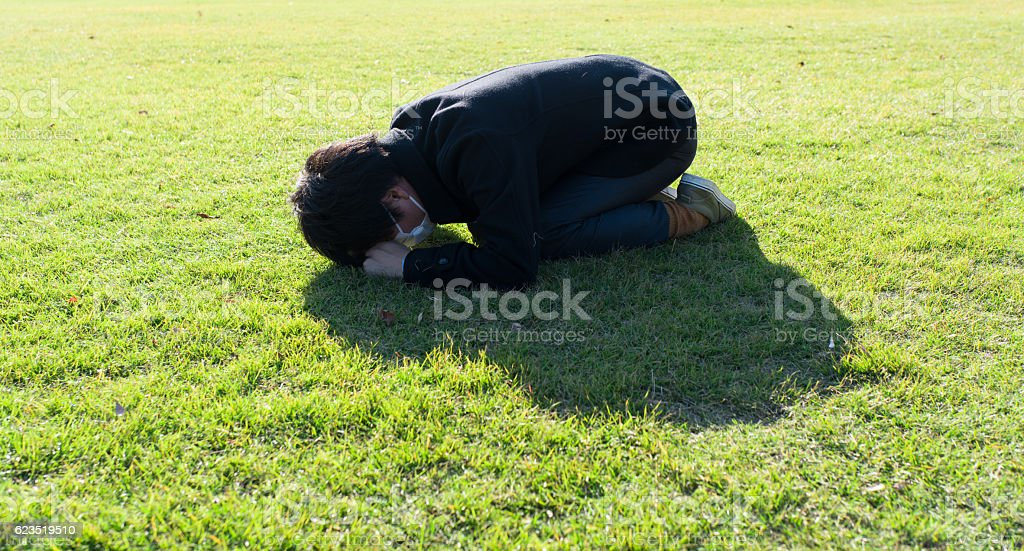 Man crouching down on the green field stock photo