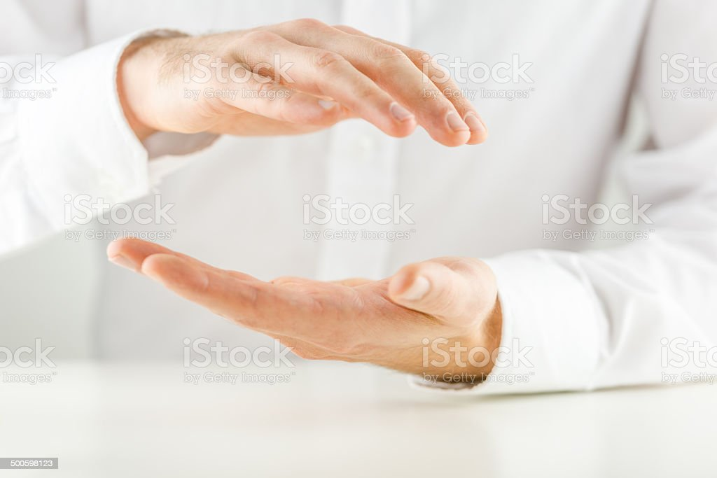 Man cupping his hands in a protective gesture stock photo