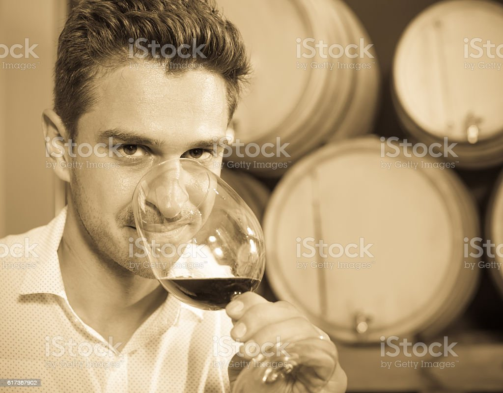 Man customer holding glass of red wine in winery section stock photo