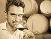 Man customer holding glass of red wine in winery section
