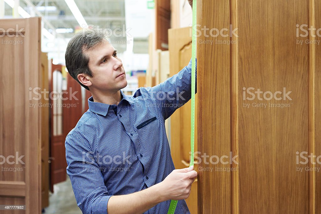 Man customer measures door to store of construction and housekee stock photo