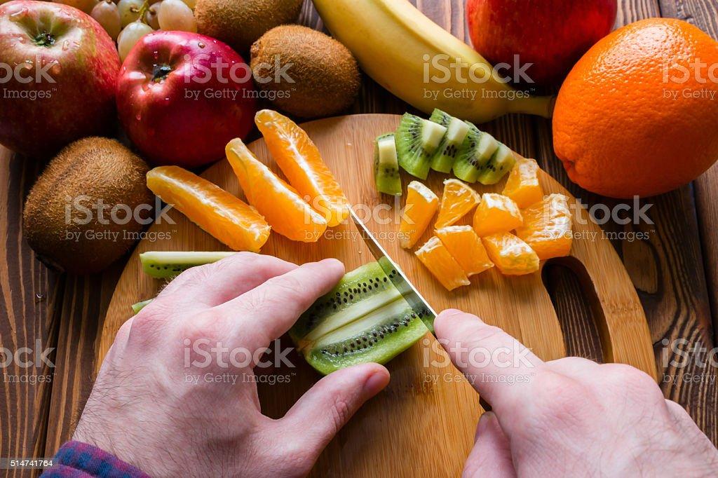 man cuts fruit on a cutting board stock photo