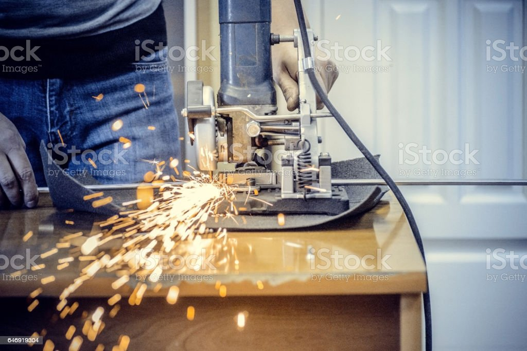 Worker man cutting a metal pipe in two pieces and lot of sparks...