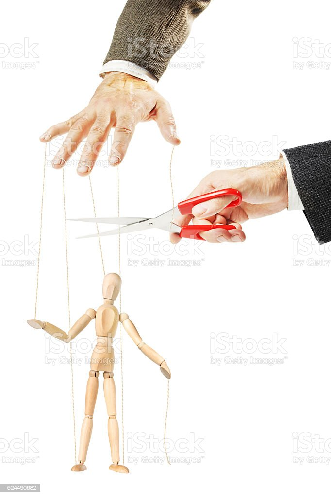 Man cuts threads of a wooden puppet. Concept of release stock photo