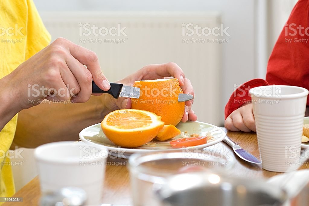 Man cutting an orange royalty-free stock photo