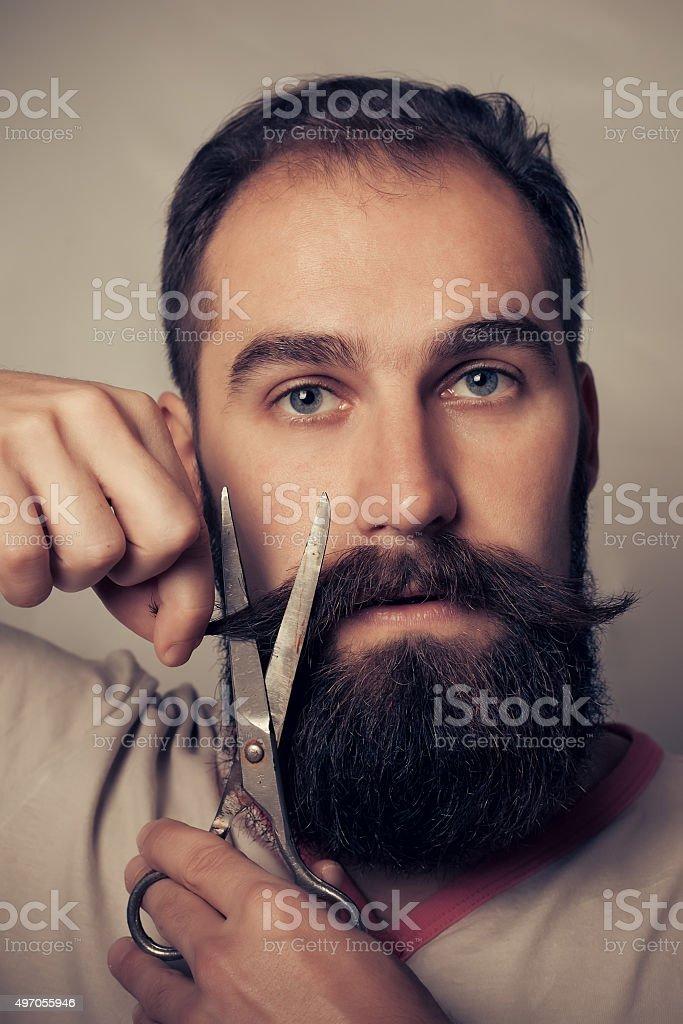 Man Cutting Beard against a grey background stock photo