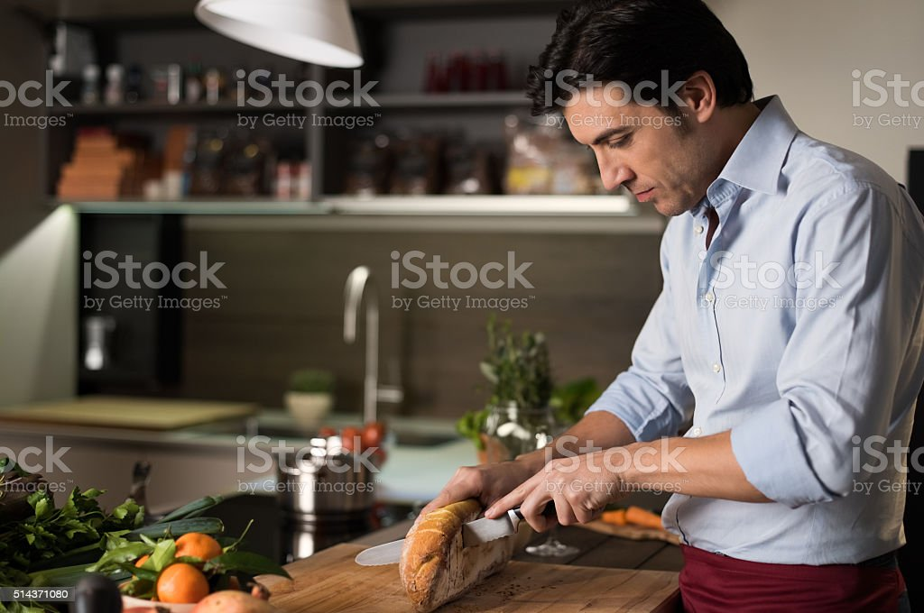 Man cutting bread stock photo