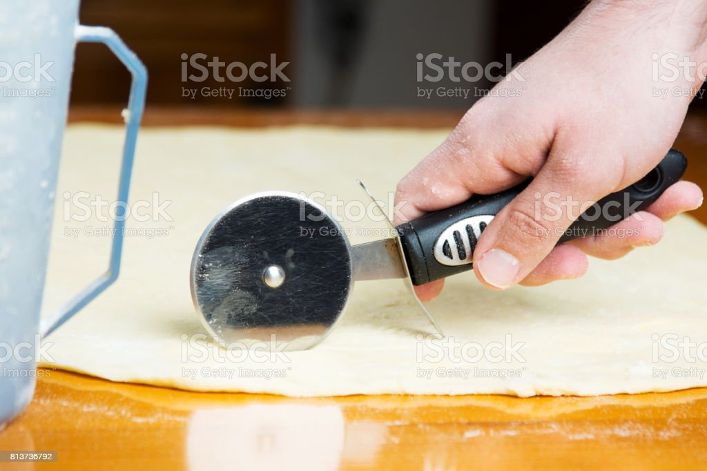 Man cutting dough with roller knife stock photo