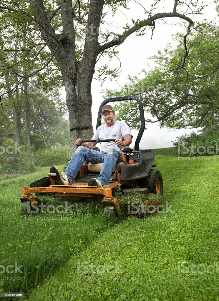 Man cutting grass on a riding lawnmower stock photo