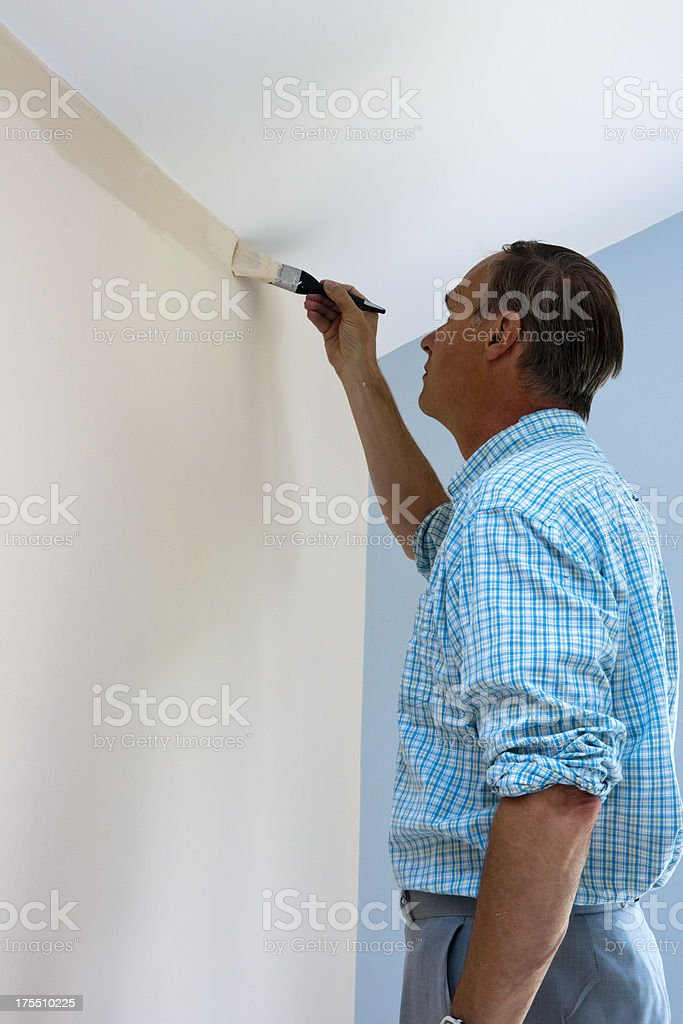 Man cutting in with a paintbrush on an internal wall stock photo