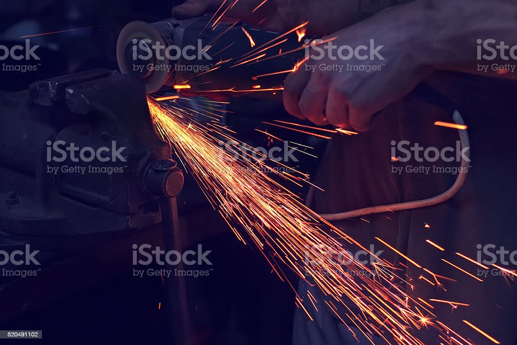 man cutting metal with angle grinder. Sparks while grinding iron stock photo