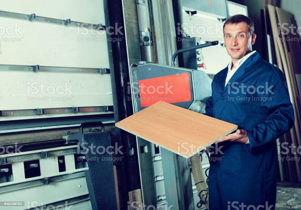 man cutting plywood with electric saw stock photo