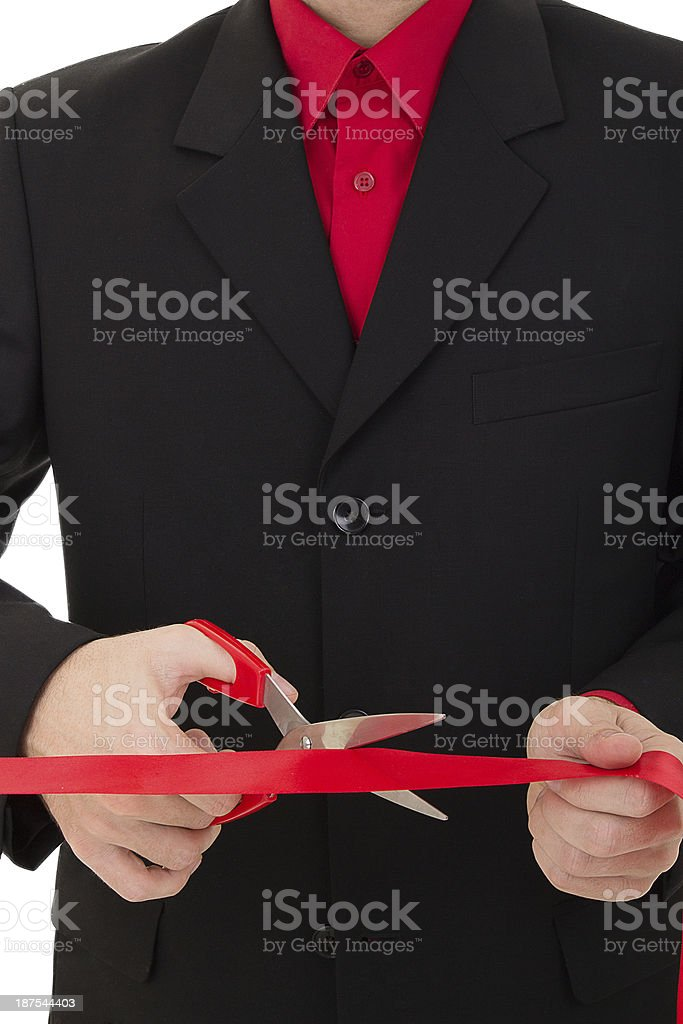 man cutting the red ribbon with scissors stock photo