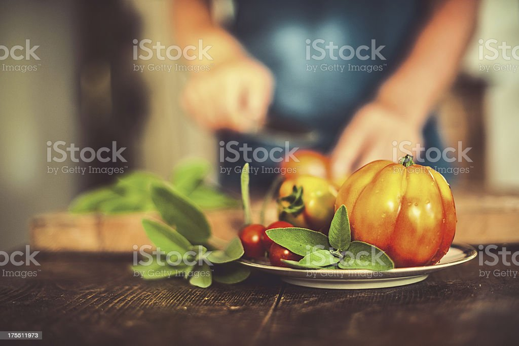 Man cutting tomatoes in rustic kitchen stock photo
