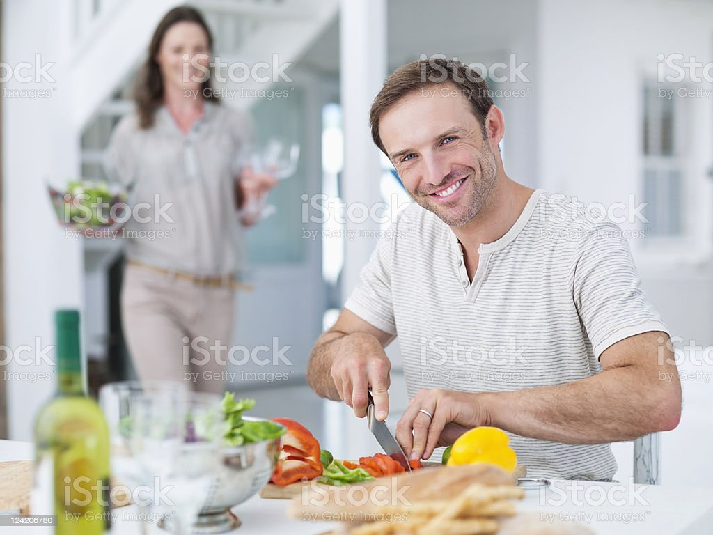 Man cutting vegetable with woman in the background royalty-free stock photo