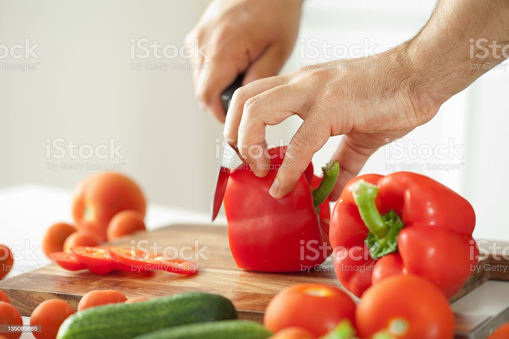 man cutting vegetables for salad stock photo