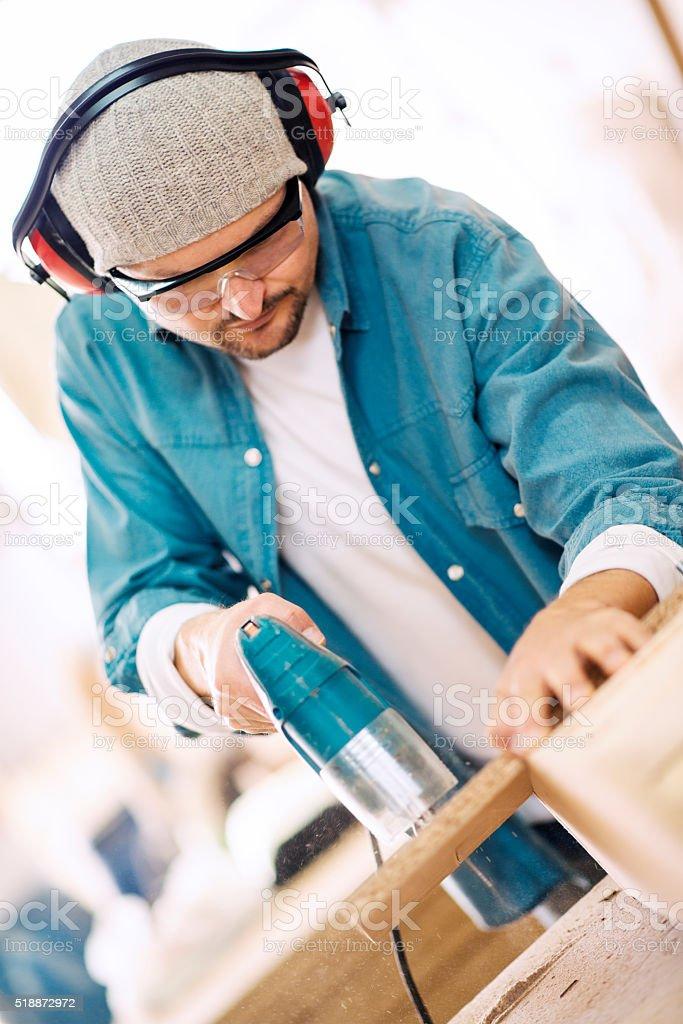 Man cutting wood plank using electric jig saw stock photo