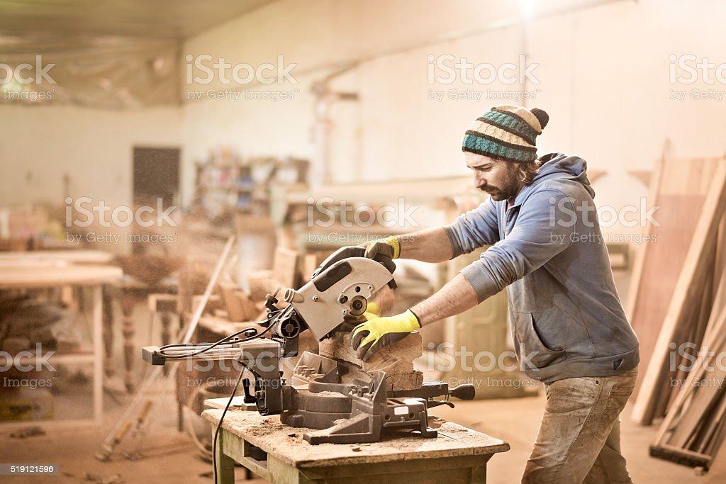 Man cutting wood with circular saw stock photo