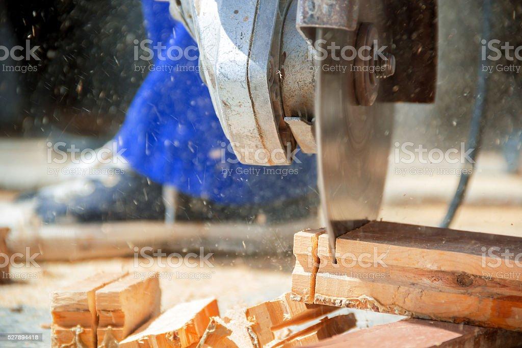 man cutting wood with saw stock photo