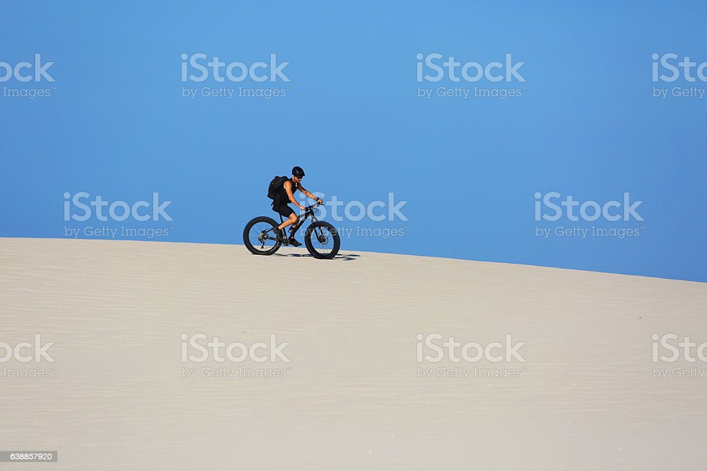 Man cycles on a sand dune on mountain bike stock photo