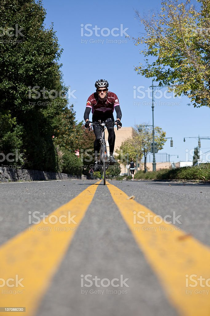 Man cycling between double yellow lines stock photo