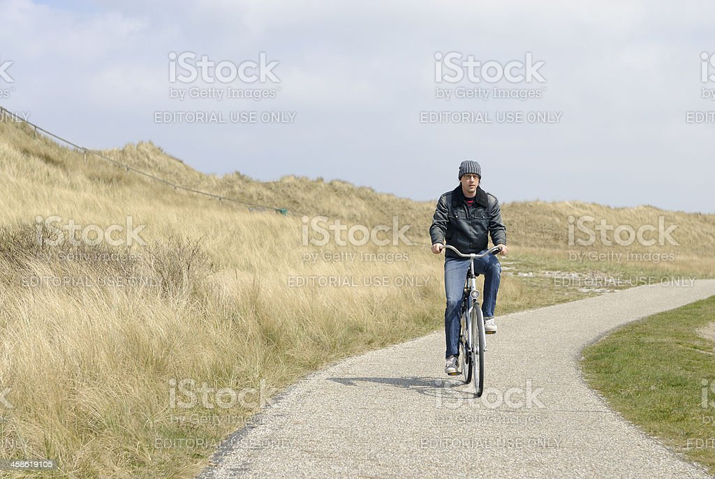 Man cycling in dune landscape royalty-free stock photo