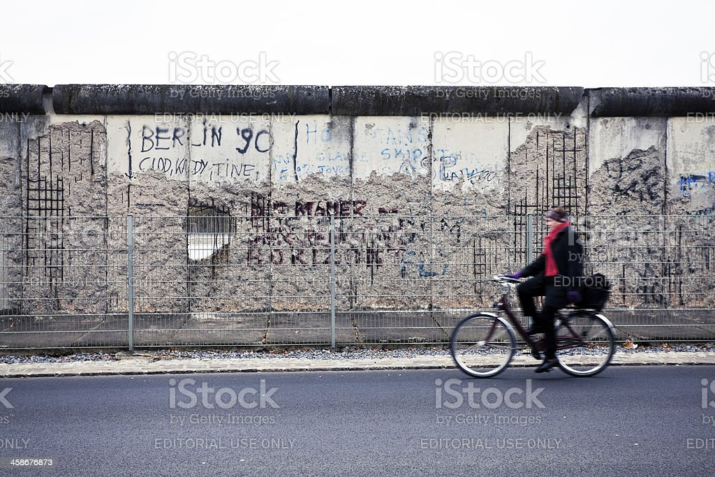 Man Cycling in Front of Berlin Wall, East Side, Germany stock photo