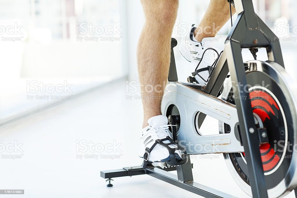 Man Cycling On Exercise Bike In Gym stock photo