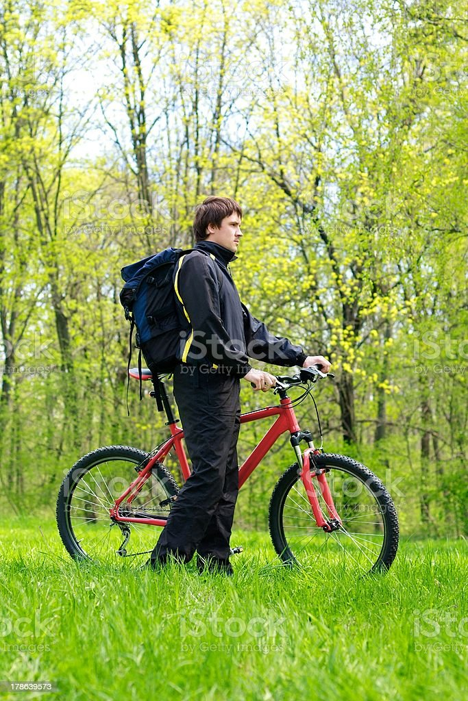 Man Cyclist with Bike and Backpack among the green nature royalty-free stock photo