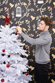 Man decorating christmas tree
