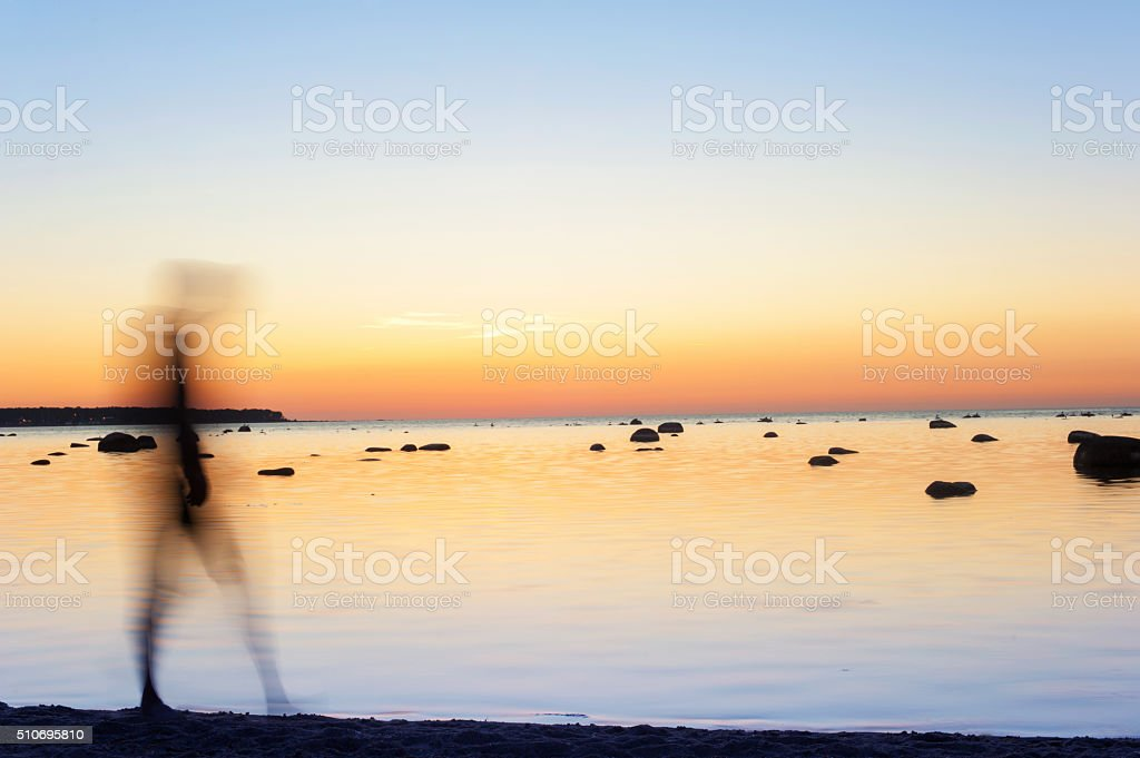 Man defocused silhouette walking on seaside at sunset stock photo