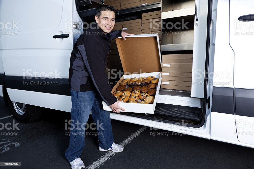 Man delivering boxes of baked goods stock photo
