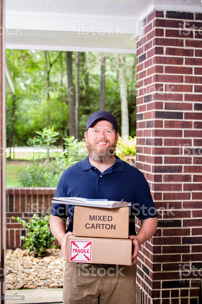 Man delivers packages to customer at home. stock photo