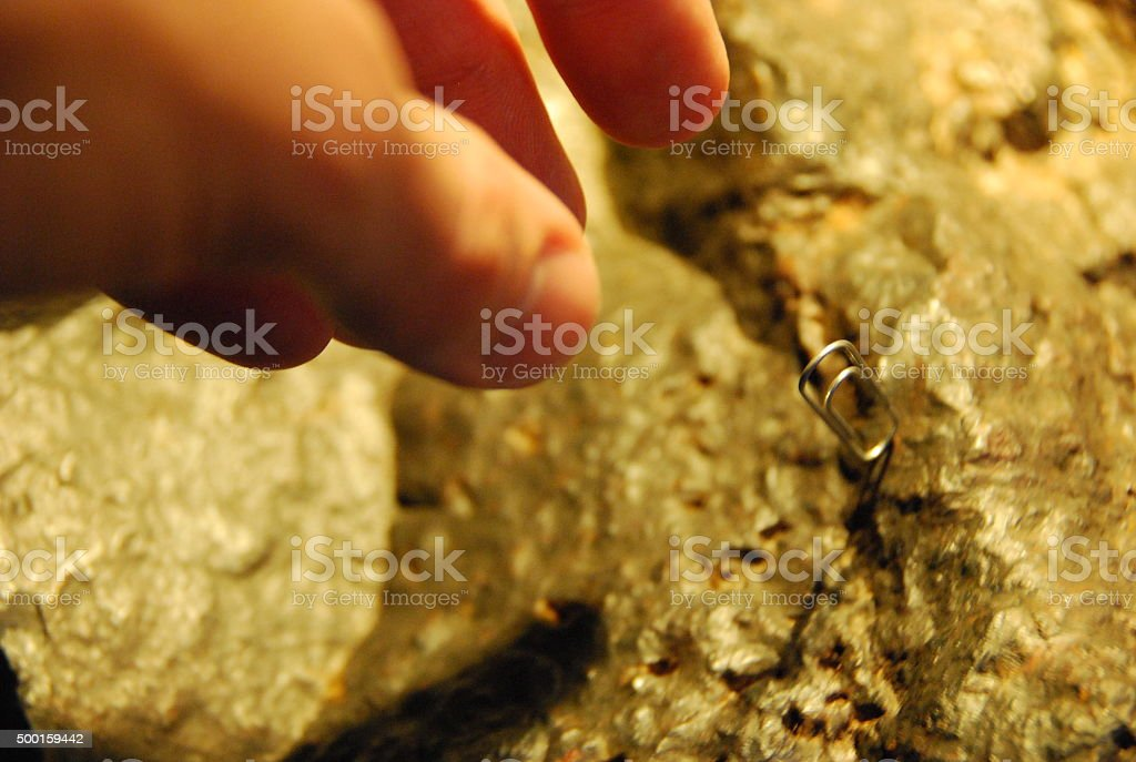 Man Demonstrating Lodestone in Action with Paperclip stock photo