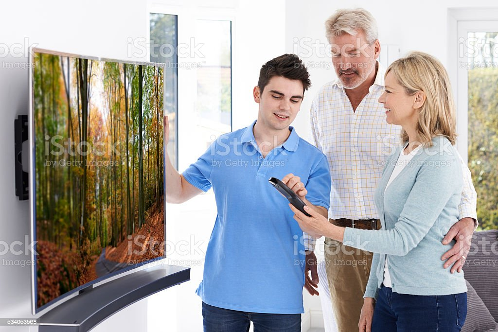 Man Demonstrating New Television To Mature Couple At Home stock photo