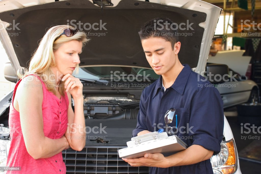 Man detailing car repairs to female owner, who isn't happy royalty-free stock photo