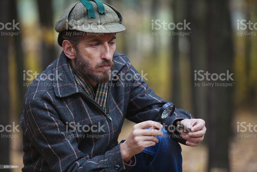 Man detective with a beard exploring tree fragment stock photo