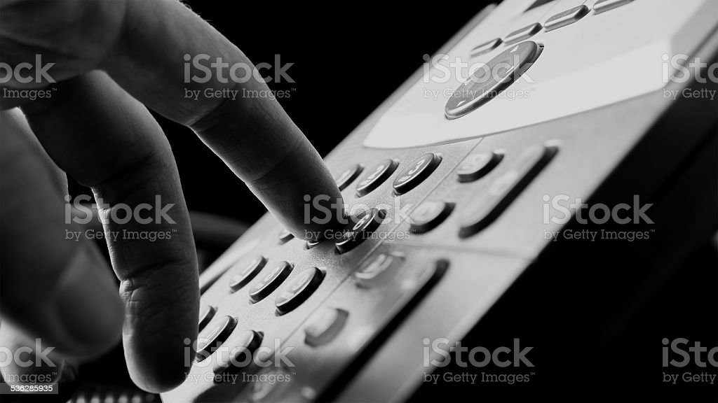 Man dialing out on a land line telephone stock photo