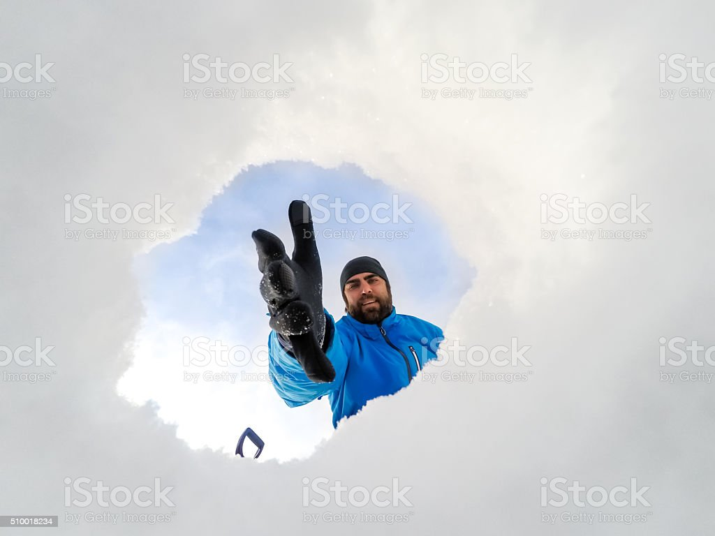 POV man digging a hole in snow view from inside stock photo