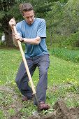 Man digging soil for garden