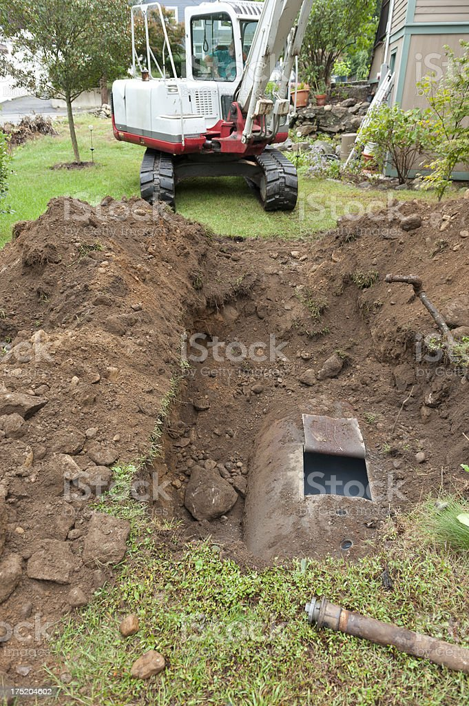 Man digging up oil tank with excavator royalty-free stock photo