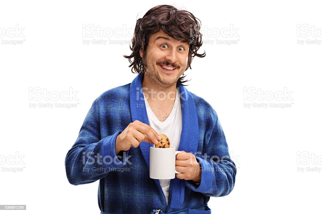 Man dipping a chocolate chip cookie in milk stock photo