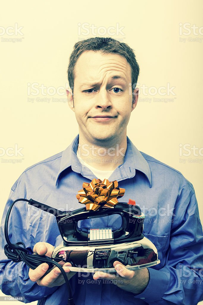 Man disappointed with iron as a gift stock photo