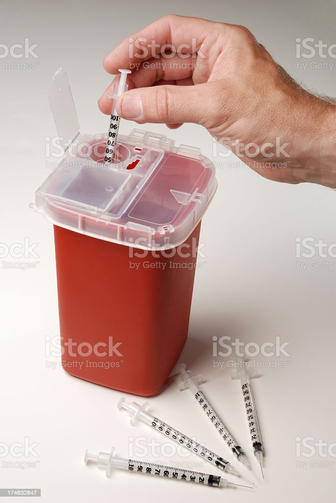 A man disposing a used syringe stock photo